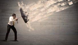 Affärsman som skyddar med paraplyet mot vind av legitimationshandlingar Fotografering för Bildbyråer