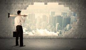 Affärsman som slår väggen med hammaren på stadssikt arkivbild