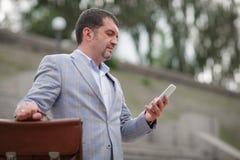 Affärsman som smsar med en telefon Direktör med portföljen på en suddig bakgrund Yrkesmässighetbegrepp kopiera avstånd Royaltyfria Foton
