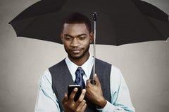 Affärsman som smsar under paraplyet royaltyfria bilder