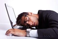 Affärsman som sovar på en bärbar datordator Royaltyfri Foto