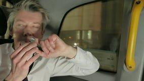 Affärsman som spelar med en rastlös människaspinnner i baksidan av en taxitaxi på natten stock video