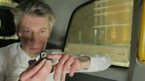Affärsman som spelar med rastlös människaspinnaren i baksidan av en taxitaxi på natten stock video