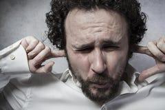 Affärsman som täcker hans öron, man i den vita skjortan med rolig exp Arkivbild