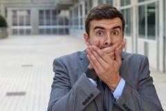 Affärsman som täcker hans mun, når framställning av ett fel Royaltyfri Bild