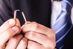 Affärsman som tänder en mycket liten firecracker Royaltyfria Bilder