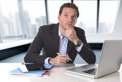 Affärsman som tänker på datorbärbar datorskrivbordet som ser reflexivt a royaltyfria foton
