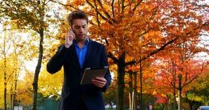 Affärsman som talar på den digitala minnestavlan för mobiltelefon och för innehav lager videofilmer