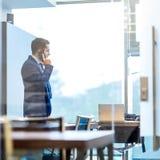 Affärsman som talar på en mobiltelefon, medan se till och med fönster Arkivfoto