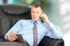 Affärsman som talar på en mobiltelefon och ett arbete på hans minnestavla Arkivfoto