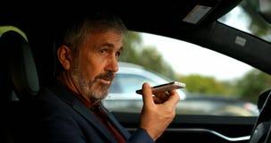 Affärsman som talar på mobiltelefonen i en bil 4k arkivfilmer