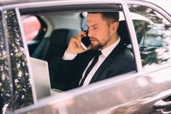 Affärsman som talar på mobiltelefonen och ser utanför fönstret, medan sitta på baksätebilen Arkivfoto