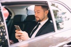 Affärsman som talar på mobiltelefonen och ser utanför fönstret, medan sitta på baksätebilen Arkivfoton