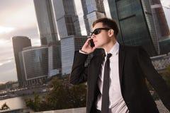 Affärsman som talar på telefonbakgrunden av arkivfoton