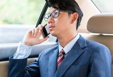 Affärsman som talar på telefonen i bil arkivfoto