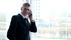 Affärsman som talar på telefonen i byggnadshall arkivfilmer