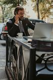 Affärsman som talar på telefonen, medan arbeta på en bärbar dator fotografering för bildbyråer