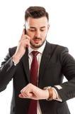 Affärsman som talar på telefonen, medan kontrollera hans klocka royaltyfri fotografi