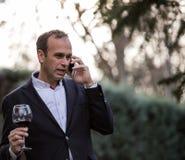 Affärsman som talar på telefonen och dricker vin royaltyfria foton