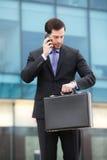 Affärsman som talar på telefonen och ser klockan Royaltyfri Foto