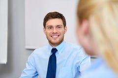 Affärsman som talar till den kvinnliga kollegan på kontoret Royaltyfri Bild