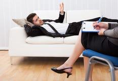 Affärsman som talar till hans psykiater som förklarar något royaltyfri bild