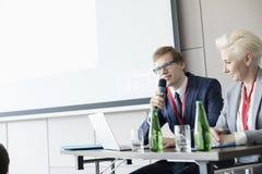 Affärsman som talar till och med mikrofonen, medan sitta på skrivbordet i konventcentrum Arkivfoto
