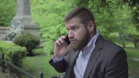 Affärsman som talar vid smartphonen som är utomhus- arkivfilmer