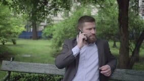 Affärsman som talar vid smartphonen som är utomhus-, pannaskott lager videofilmer