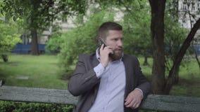 Affärsman som talar vid smartphonen som är utomhus-, pannaskott stock video