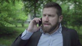 Affärsman som talar vid smartphonen, utomhus- nära skott arkivfilmer