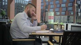 Affärsman som talar vid telefonen och gör anmärkningar i dokument steadicam arkivfilmer