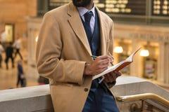 Affärsman som tar anmärkningen genom att använda det bärande kaschmiromslaget för penna och för notepad och affärsdräkten arkivbild