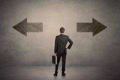 Affärsman som tar ett beslut, medan stå framme av två gr Arkivfoto