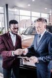 Affärsman som tar pennan för undertecknande avtal, medan köpa bilen royaltyfri bild