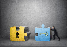 Affärsman som tillsammans drar tangent- och nyckelhålstycken av pusslet Fotografering för Bildbyråer