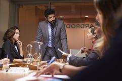 Affärsman som tilltalar upp laget på ett möte, slut för låg vinkel arkivfoto