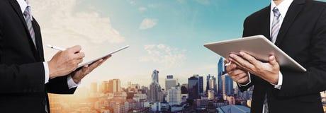 Affärsman som två arbetar på den utomhus- digitala minnestavlan och panorama- bakgrund för stad som föreställer medarbetare, part Royaltyfri Bild