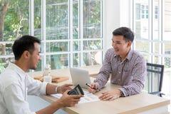 Affärsman som två plattar till data på mötet Meetin för affärsfolk arkivbild