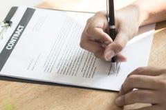 Affärsman som undertecknar på avtalspapper på tabellen efter accepterad de royaltyfria foton