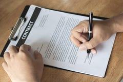 Affärsman som undertecknar på avtalspapper på tabellen efter accepterad de arkivfoto