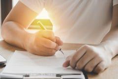 Affärsman som undertecknar på avtalspapper på tabellen efter accepterad de fotografering för bildbyråer