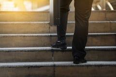 Affärsman som upp klättrar en konkret trappuppgång arkivbild