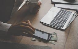 Affärsman som ut använder mobiltelefonen till pengar för kassa på kontor D royaltyfri foto