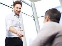 Affärsman som ut når för en handskakning Arkivbilder