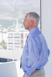 Affärsman som ut ser fönstret Fotografering för Bildbyråer
