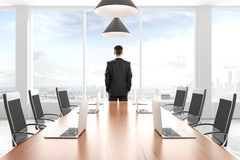Affärsman som ut ser fönstret i modern intelligens för konferensrum Royaltyfria Bilder