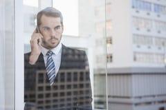 Affärsman som ut ser fönstret på telefonen Arkivbild