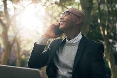 Affärsman som utomhus använder bärbar dator- och mobiltelefonsammanträde royaltyfri bild