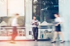 Affärsman som utomhus använder ett digitalt minnestavlakontor och suddigt P royaltyfri foto